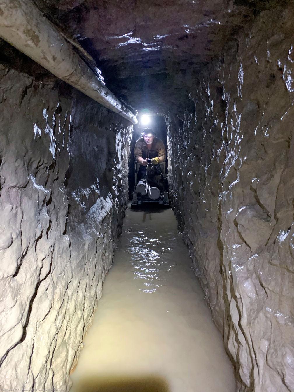 Agente da alfândega e proteção de fronteiras se apoia em carrinho que transporta cilindros de oxigênio no mais longo túnel encontrado na fronteira entre EUA e México — Foto: Departamento de Proteção de fronteiras e alfândega dos EUA/ via Reuters