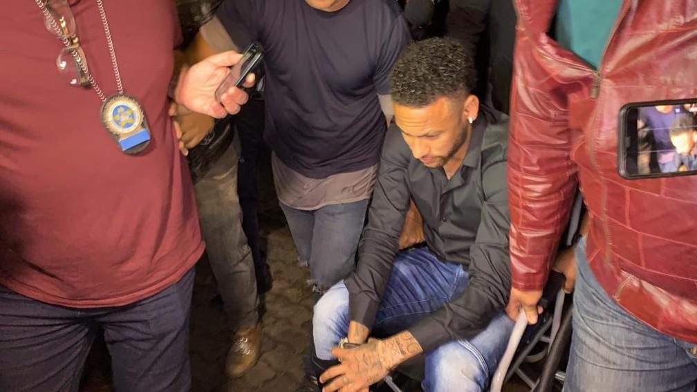 Neymar usou muletas e depois uma cadeira de rodas para se locomover na Cidade da Polícia — Foto: Matheus Rodrigues/G1