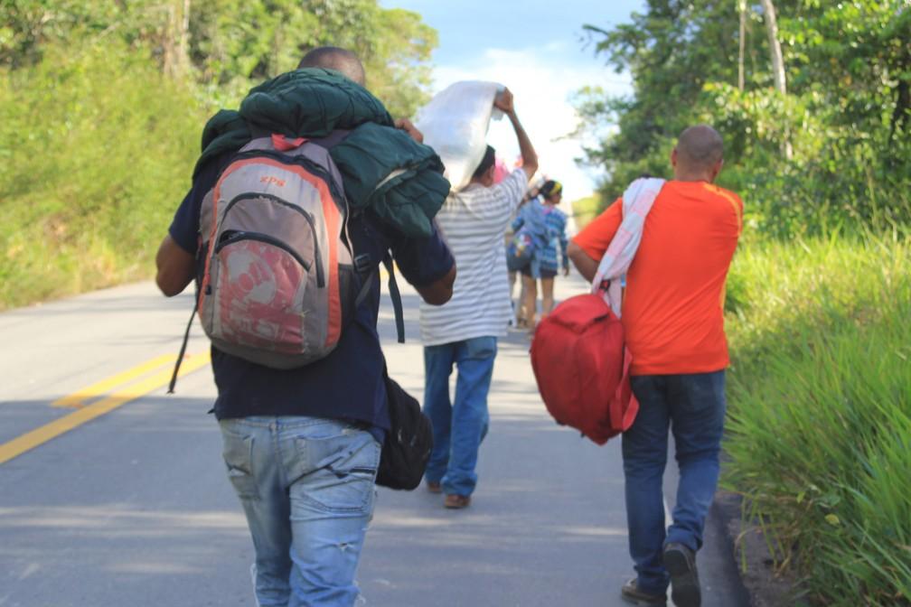 Imigrantes carregam malas e caminham pela BR-174, que liga Brasil e Venezuela (Foto: Emily Costa/G1 RR/Arquivo)
