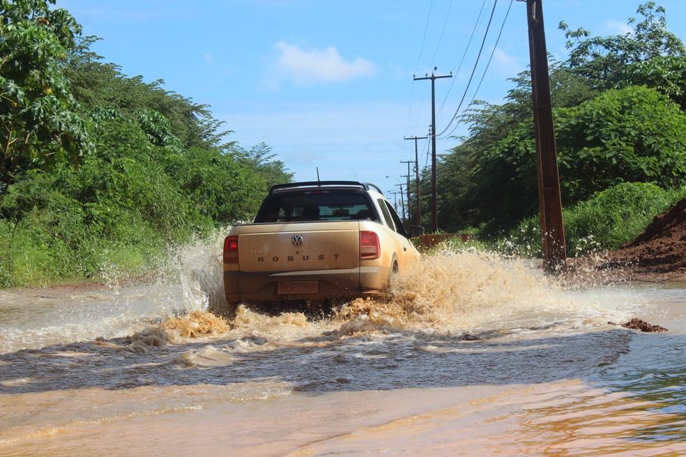 Moradores tentam driblar água do rio na estrada do Belmont — Foto: Cássia Firmino/G1