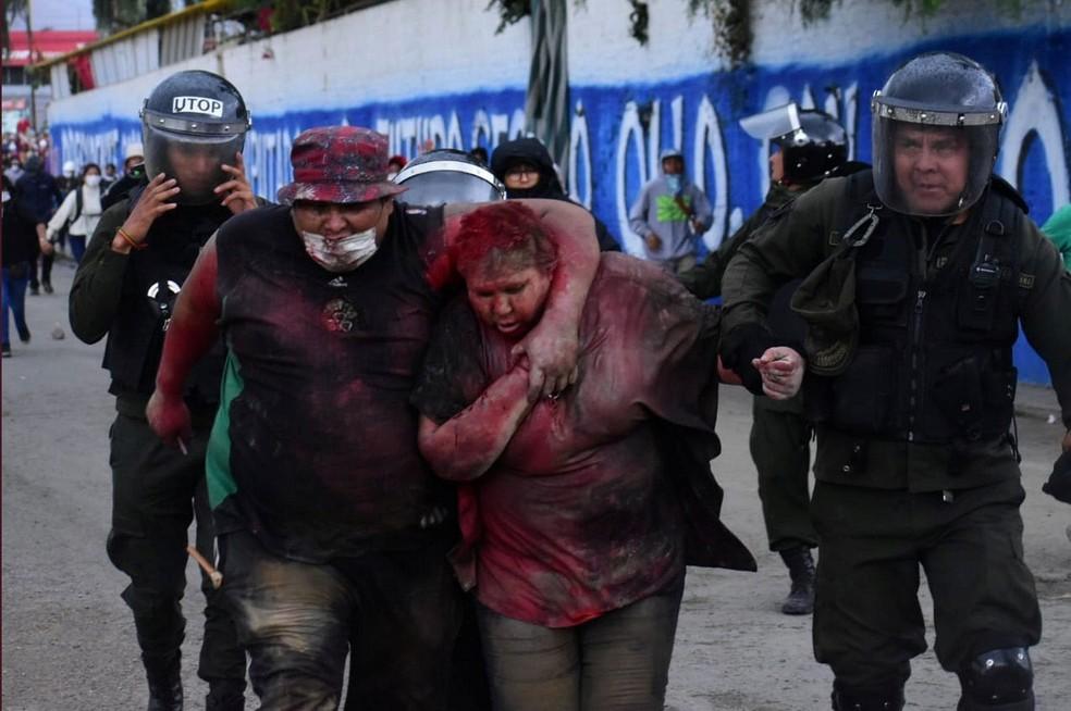 Patricia Arce, prefeita de Vinto, é resgatada por policiais; manifestantes incendiaram a prefeitura, jogaram tinta vermelha em Arce e cortaram seus cabelos — Foto: Daniel James/Los Tiempos Bolivia/via Reuters