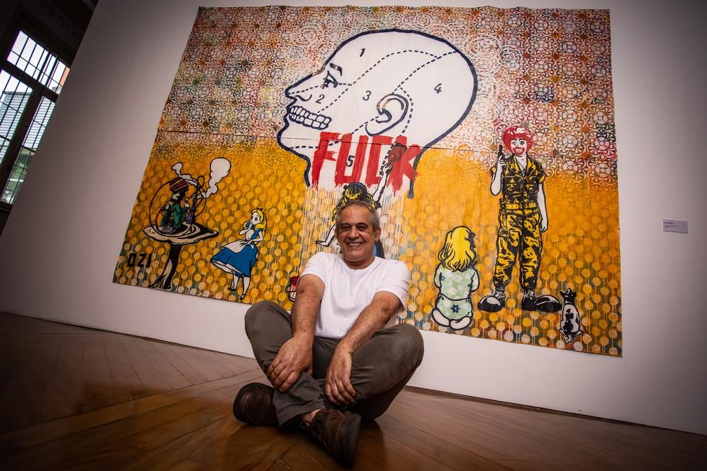 O grafiteiro Ozi posa diante de uma de suas grandes obras expostas na mostra retrospectiva de seus 35 anos de carreira na Chácara Lane, na Zona Central de São Paulo — Foto: Fábio Tito/G1