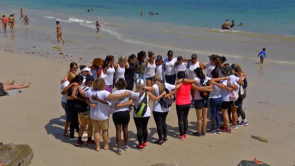 Após refazer o caminho feito Fabiane, grupo deu um abraço coletivo na praia de Arraial do Cabo, no RJ — Foto: Reprodução / Inter TV