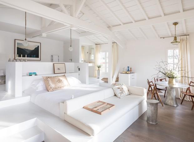 Tudo no quarto é branco, exceto o antigo guarda-roupa de madeira e as cadeiras Hans Wegner, que trazem cor à suíte. (Foto: Divulgação)
