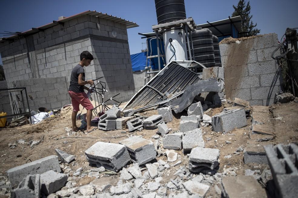 Um menino palestino verifica os danos à casa de sua família após ataques aéreos israelenses no campo de refugiados de Buriej, na Faixa de Gaza, no sábado (15) — Foto: Khalil Hamra/AP