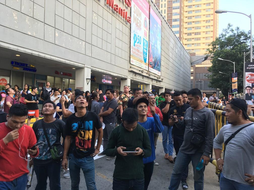 Depois do terremoto, pessoas se aglomeram do lado de fora de um shopping center em Manila, a capital das Filipinas — Foto: Ted Aljibe / AFP