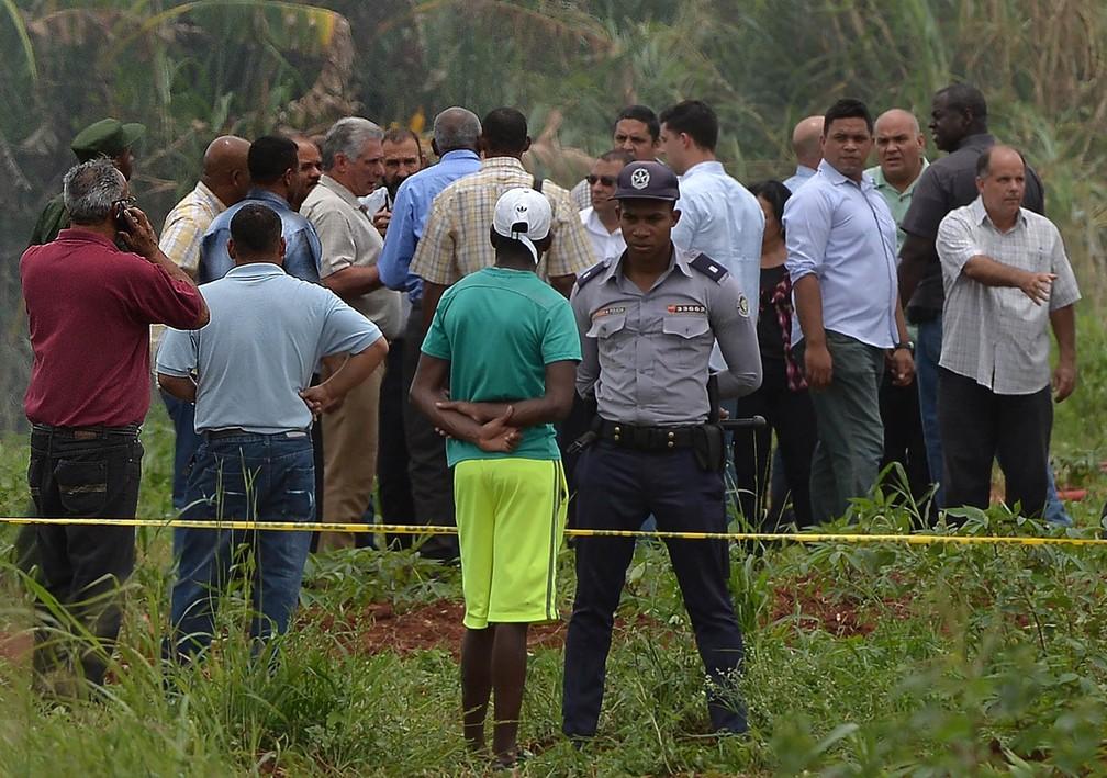 Policial guarda perímetro isolado do público enquanto, ao fundo, o presidente de Cuba, Miguel Diaz-Canel, conversa com um grupo após chegar ao local do acidente aéreo em Havana (Foto: Yamil Lage/AFP)