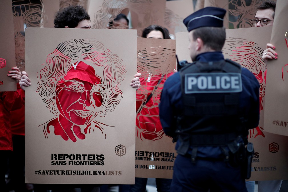 5 de janeiro - Integrantes do Reporters Without Borders (Repórteres Sem Fronteirs) exibem cartazes feitos pelo artista de rua francês C215 com retratos de jornalistas turcos presos durante uma manifestação em frente à embaixada turca em Paris, na França (Foto:  Benoit Tessier/Reuters)