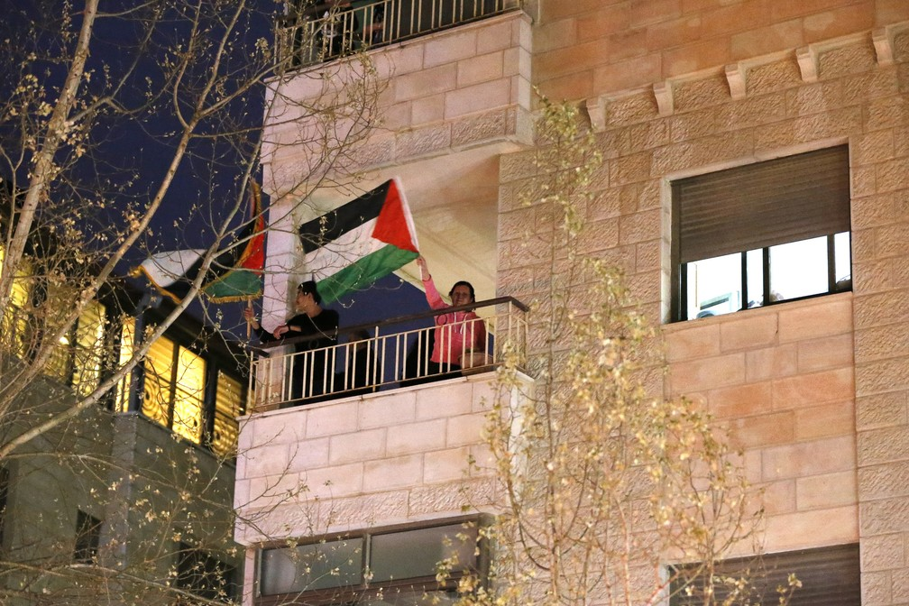 Palestinos comemoram o Dia da Terra Palestina agitando bandeiras de suas varanda em Ramallah, na Cisjordânia ocupada, em 30 de março, em vez das marchas de rua que foram canceladas devido à pandemia do COVID-19 — Foto:  Abbas Momani/AFP