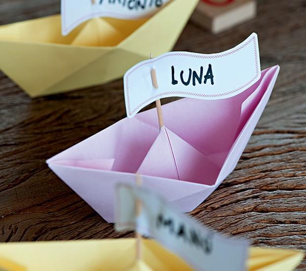 Para marcar o lugar de cada um na festa infantil, barcos de papel com bandeirinhas no palito (Foto: Foto Iara Venanzi | Realização Cláudia Pixu | Produção Luana Prade)