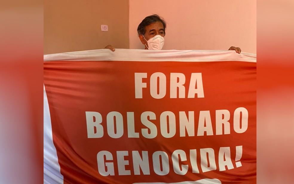 Professor Arquidones Bites exibe faixa que estava amarrada no capô do carro — Foto: Honório Jacometto/TV Anhanguera