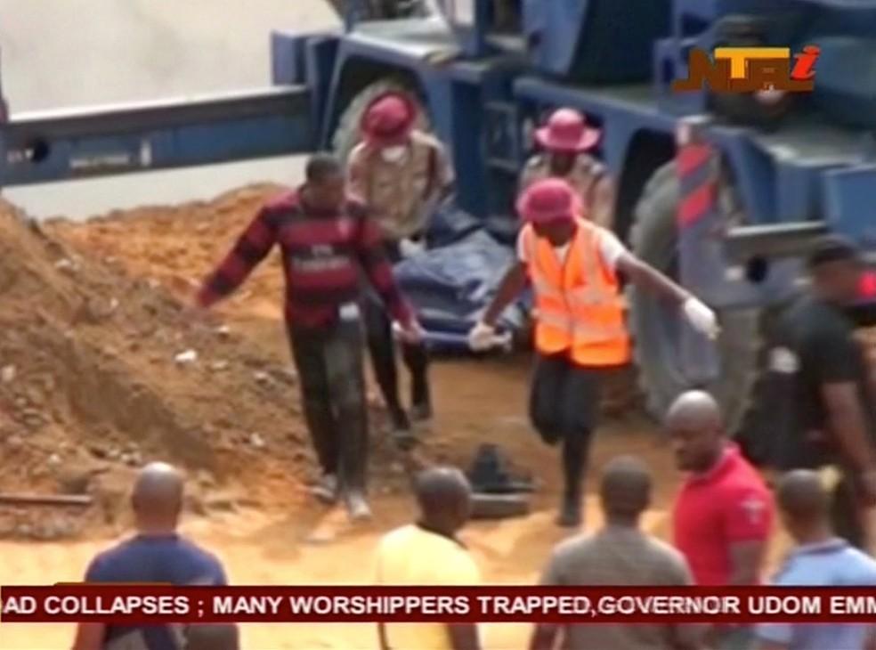 Imagem da TV mostra pessoas carregando um corpo depois do desabamento de uma igreja na cidade de Uyo, no estado de Akwa Ibom, na Nigéria (Foto: NTA via Reuters)