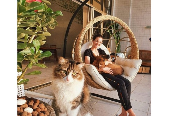 Camila Queiroz posa em sua varanda com balanço e móveis rústicos (Foto: Reprodução)