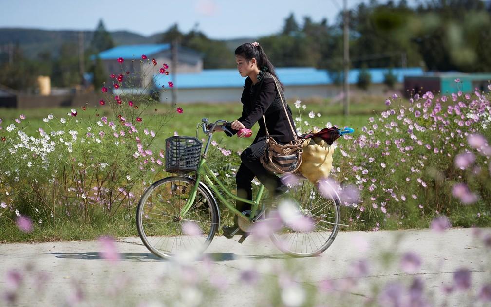 Jovem carrega compras em bicicleta na cidade de Wonsan, na Coreia do Norte, em foto de outubro de 2016  (Foto: Christian Peterson-Clausen/Handout via Reuters)