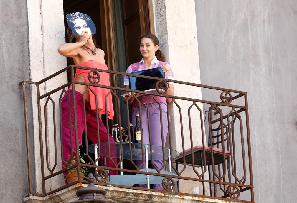 Em Catania, na Itália, uma mulher faz performance no balcão de casa, em 5 de abril de 2020 — Foto: Antonio Parrinello/Reuters
