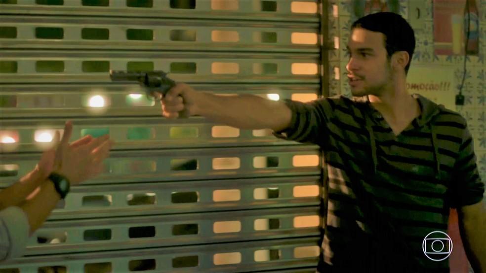 Jacaré (Sérgio Malheiros) ameaça atirar em Eliza (Marina Ruy Barbosa) e Jonatas (Felipe Simas) — Foto: TV Globo