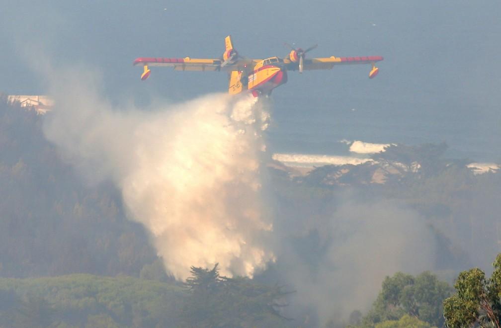 Avião atua no combate a incêndio perto da cidade de Charneca, em Portugal, neste domingo (7)  — Foto: Armando Franca/ AP