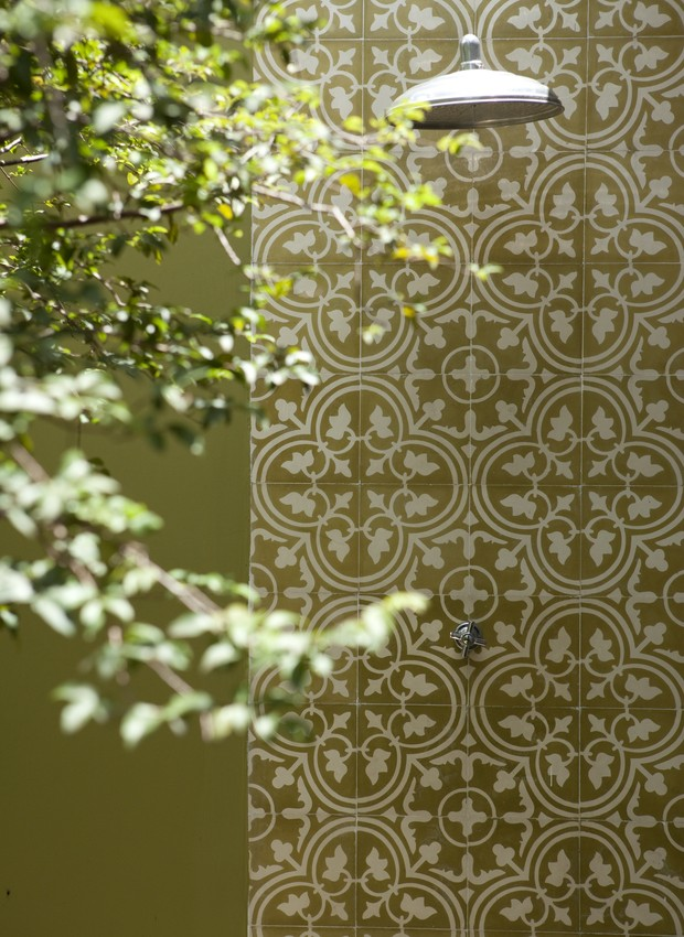 Para destacar a área do chuveirão na parede verde, a moradora escolheu o revestimento de ladrilho hidráulico, o mesmo do piso da cozinha, integrada ao jardim por portas de correr com vidro (Foto: Edu Castello/Casa e Jardim)