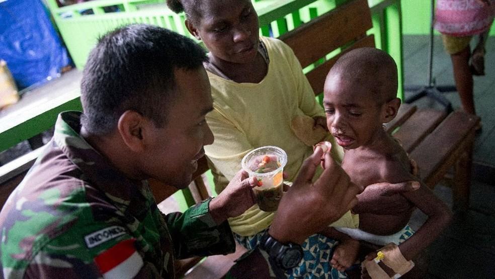 Membro do exército da Indonésia atende uma criança no hospital em Agats (Foto: AFP)