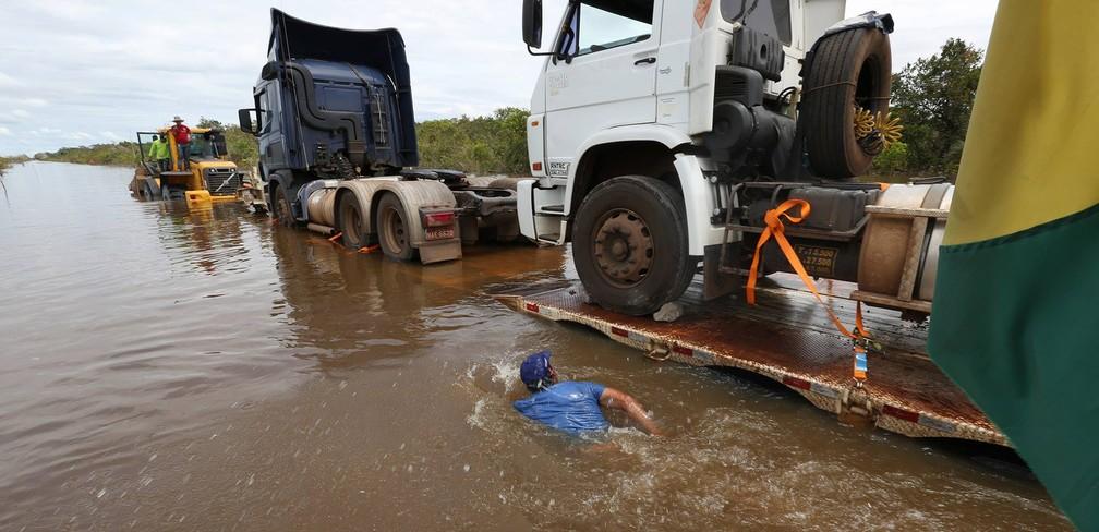 Homem nada ao lado de carretas na BR-364, inundada pelo Rio Madeira, em 2014 — Foto: Sérgio Vale/Secom Acre/Arquivo