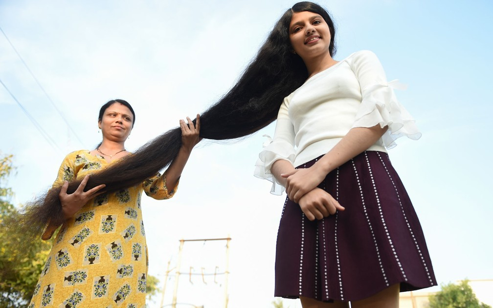 Nilanshi Patel, de 17 anos, exibe ao lado da mãe seus cabelos com 1,90 m de comprimento, que garantiram que ela fosse incluída no Livro Guinness dos Recordes, em Modasa, na Índia, no domingo (19) — Foto: Sam Panthaky/AFP