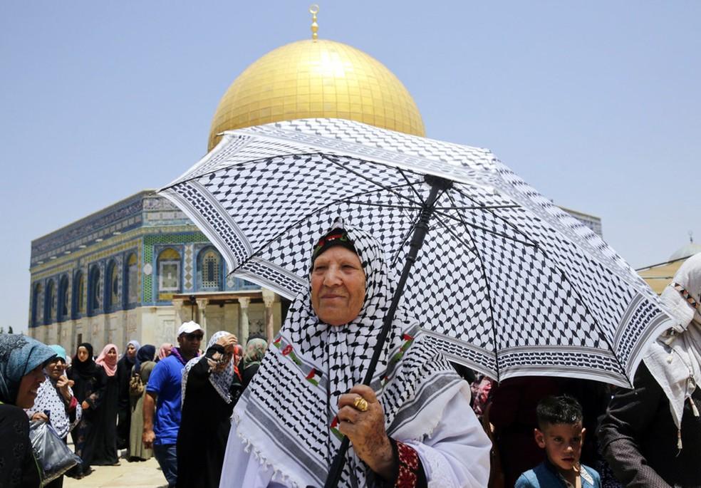 Mulheres palestinas caminham em frente ao santuário Domo da Rocha em Jerusalém durante o último dia do mês sagrado do Ramadã (Foto: Mahmoud Illean/AP)