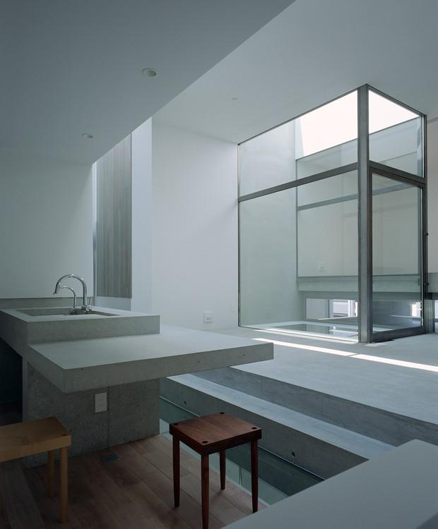 Na cozinha, uma abertura maior e central também funciona como estratégia para espalhar a luz que incide sobre a casa. De concreto, com piso de madeira, os volumes das estruturas do ambiente dividem o cômodo (Foto:  Katsuya Taira/Studio Rem/ Deezen / Reprodução)