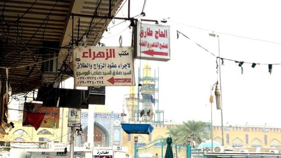 Placas apontam para escritórios de casamentos temporários em Kadhimiya — Foto: BBC