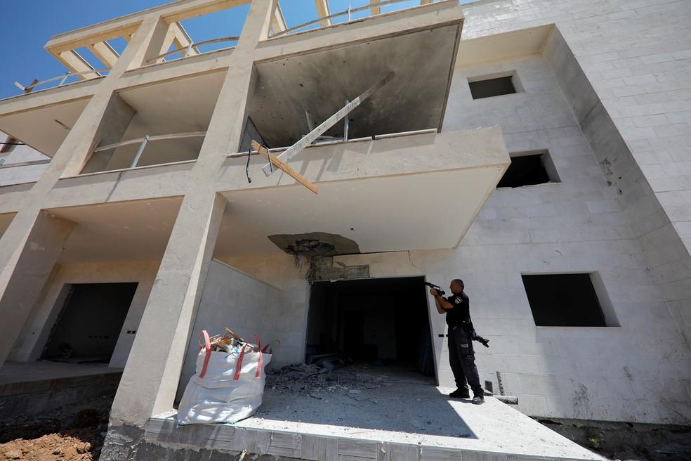 -  Policial israelense mostra dano causado por foguete palestino em construção na cidade de Sderot  Foto: Amir Cohen/Reuters