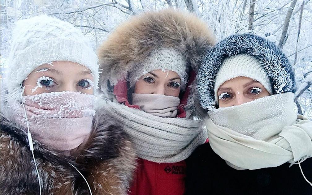 Anastasia Gruzdeva (esquerda) e amigas mostram cílios congelados pelo frio de cerca de - 50 º C na região de Yakutia, na Rússia, em foto de domingo (14) (Foto: sakhalife.ru photo via AP)