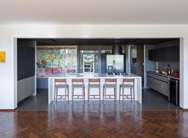 COZINHA | A grande bancada de Corian abriga pia e fogão e funciona como uma ilha prática para refeições (Foto: Joana França/Divulgação)