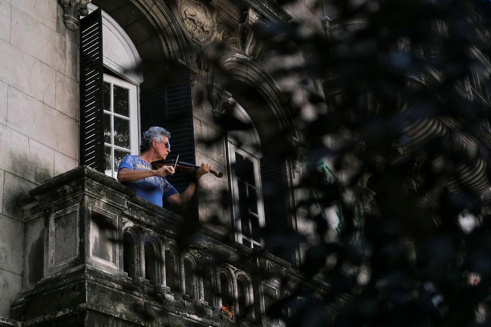 Adelmo Carvalho, de 55 anos, toca violino na varanda durante o isolamento para evitar a propagação da doença por coronavírus (COVID-19) no Rio de Janeiro  — Foto: Ricardo Moraes/Reuters