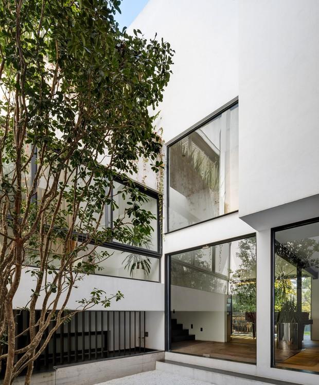 Janelas grandes são voltadas a um jardim central. Dali, os diferentes níveis da construção podem ser observados, o que valoriza a planta arquitetônica (Foto:  Rafael Gamo/ Reprodução)