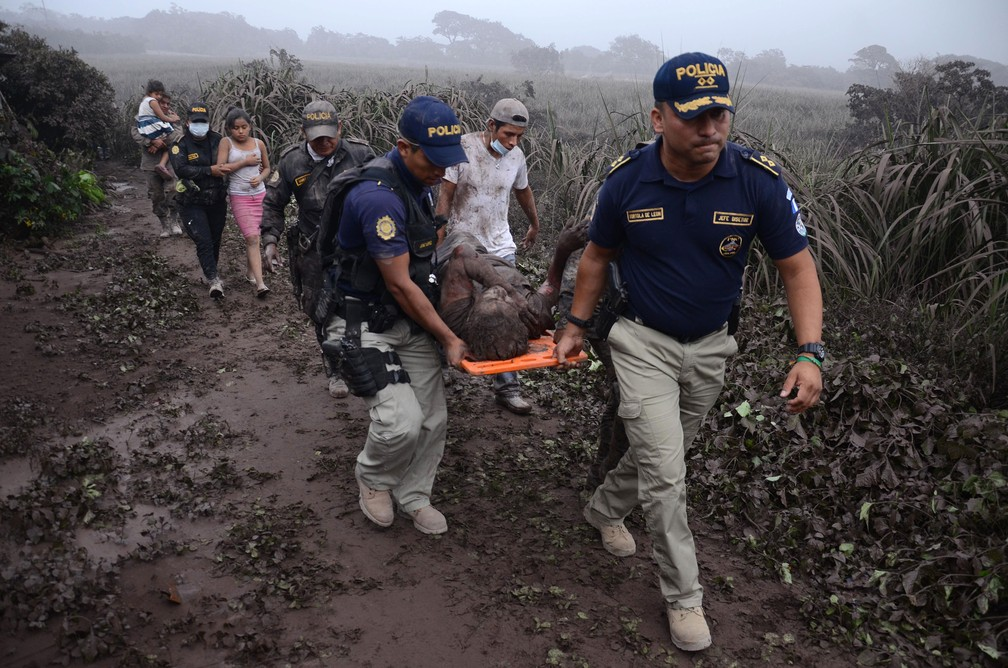 Policiais carregam ferido na erupção do Vulcão de Fogo, em El Rodeo, no departamento de Escuintla, no domingo (3)  (Foto: Noe Perez / AFP)