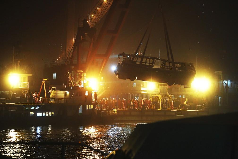 Ônibus é erguido após cair no rio Yangtze, na China, nesta sexta-feira (2). — Foto: Xinhua/AP