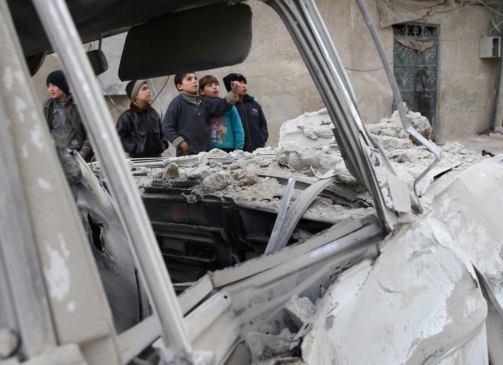 4 de janeiro - Garotos são visto perto de local destruído após ataque aéreo na cidade de Misraba, na Síria (Foto: Bassam Khabieh/Reuters)