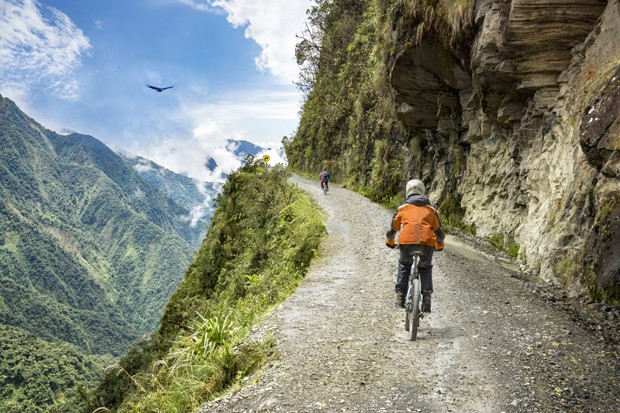 """Bike adventure travel photo. Bike tourists  ride on the """"road of death""""  downhill track  in Bolivia. In the background sky circles a condor over the scene. (Foto: Getty Images/iStockphoto)"""