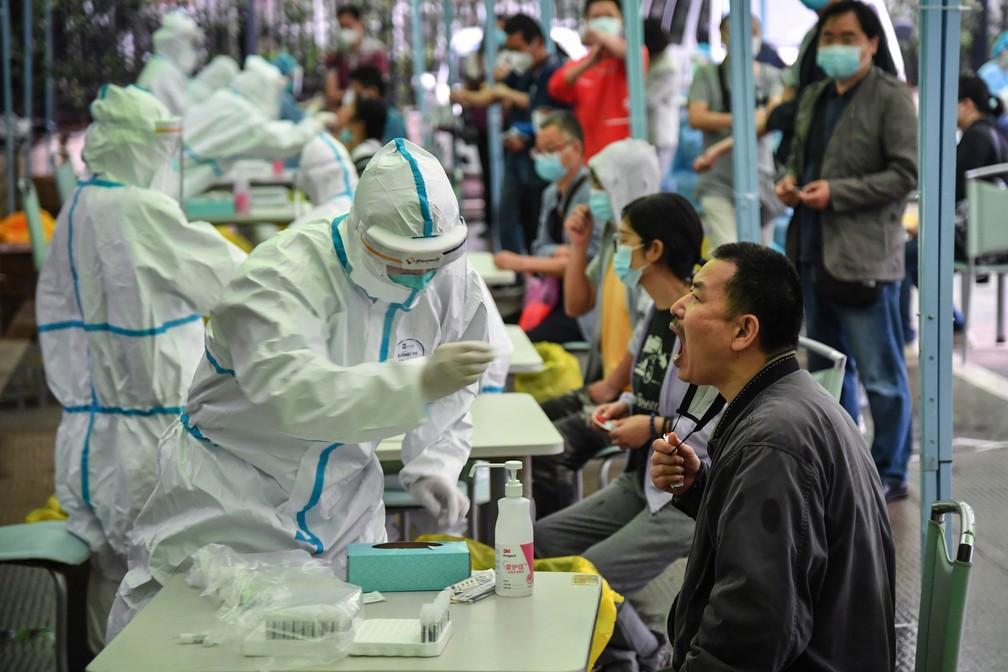 Profissional da saúde retira material para exame para detectar o novo coronavírus em Wuhan, na China, nesta quinta-feira (14)  — Foto: AFP