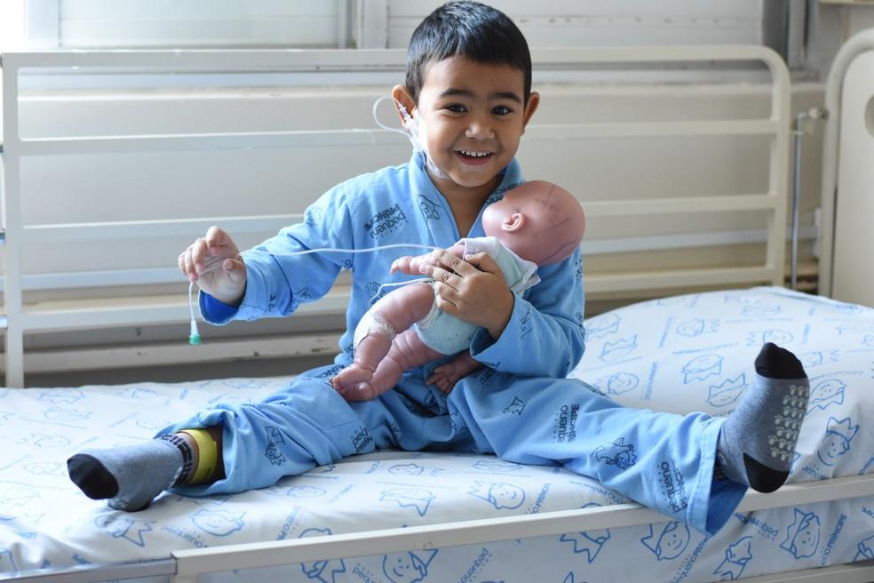 Artur brinca de fazer exames de sangue e de colocar cateter em Murilo, seu boneco — Foto: Camila Mendes/Divulgação Hospital Pequeno Príncipe