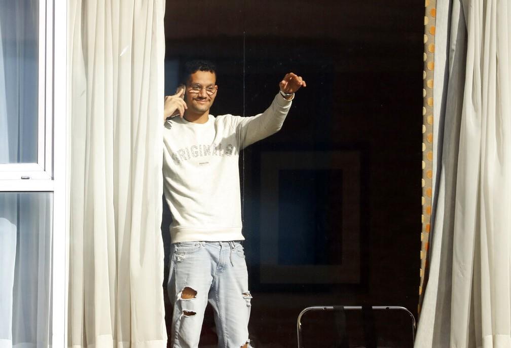 Roger Gonçalves, que é do Brasil e viajou por Madri para chegar ao Reino Unido, acena da janela do Hotel Radisson — Foto: Alastair Grant/AP