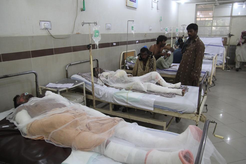 Em hospital de Bahaw, no Paquistão, pessoas são tratadas após sofrer queimaduras em acidente que deixou mais de 140 mortos. (Foto: SS MIRZA / AFP)