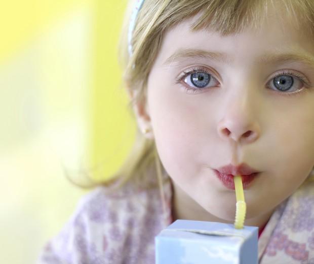 Menina bebendo suco de caixinha (Foto: Thinkstock)