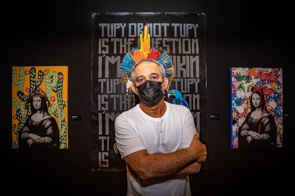 O grafiteiro Ozi posa diante de algumas de suas releituras da Mona Lisa, expostas na mostra retrospectiva de seus 35 anos de carreira na Chácara Lane, na Zona Central de São Paulo — Foto: Fábio Tito/G1