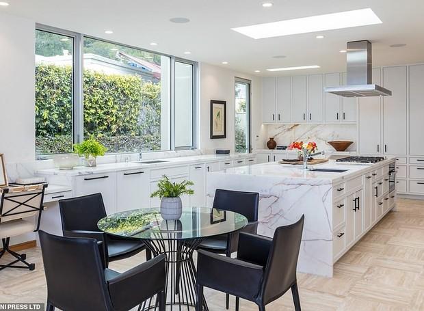 A cozinha é iluminada por janelas grandes e os móveis brancos a deixam com um ar moderno e arejado (Foto: MLS/ Reprodução)