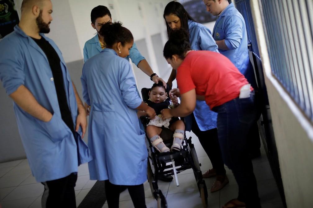 Jackeline Vieira de Souza (de vermelho), 28, mãe de Daniel Vieira, que tem dois anos de idade e nasceu com microcefalia, durante uma sessão de fisioterapia na APAE, no Recife — Foto: Ueslei Marcelino/Reuters