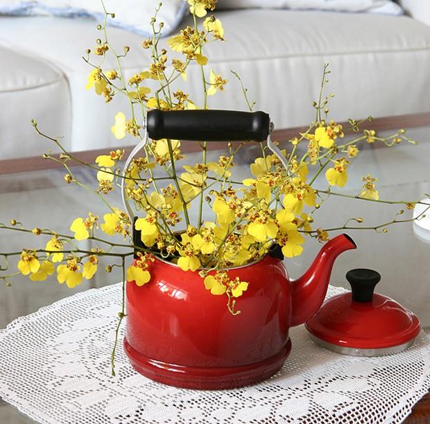 Quer descontrair? Crie um vaso novo para a sua flor. Esta chuva-de-ouro ficou charmosa dentro de uma chaleira esmaltada vermelha (Foto: Evelyn Müller)