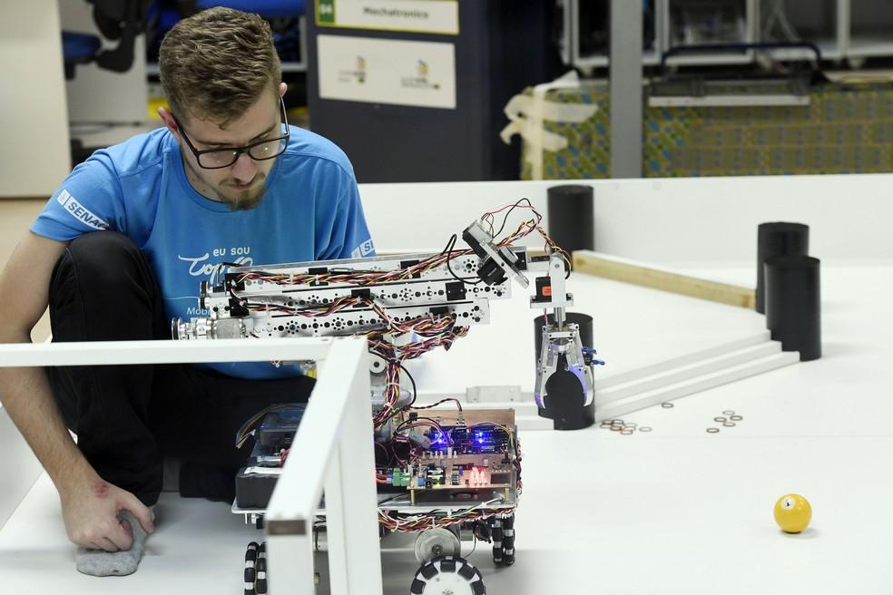 Homem trabalha na programação de robô (Foto: José Paulo Lacerda/CNI)