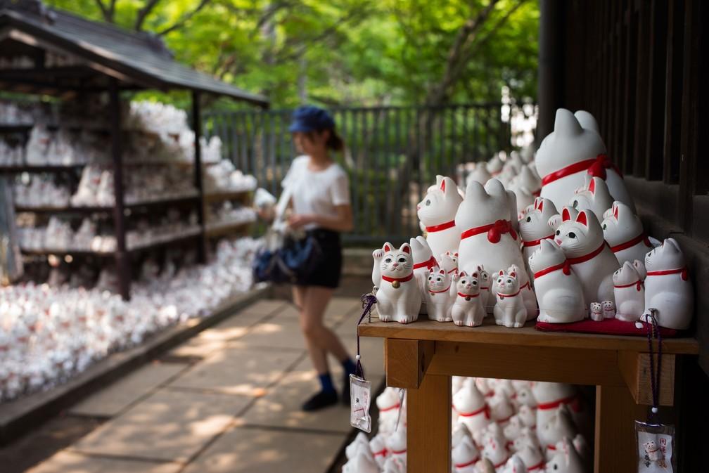 Mulher caminha entre gatos 'maneki-neko' no templo Gotokuji, em Tóquio  (Foto: Martin Bureau / AFP)
