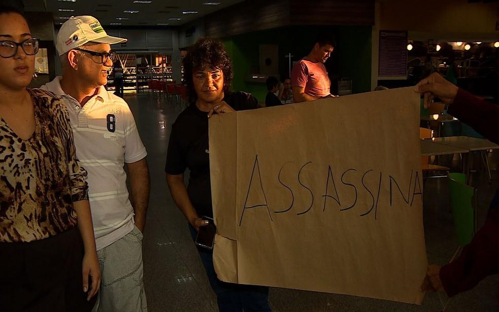 Parentes do policial morto estiveram no aeroporto com um cartaz em protesto (Foto: Reprodução/TV Sergipe)