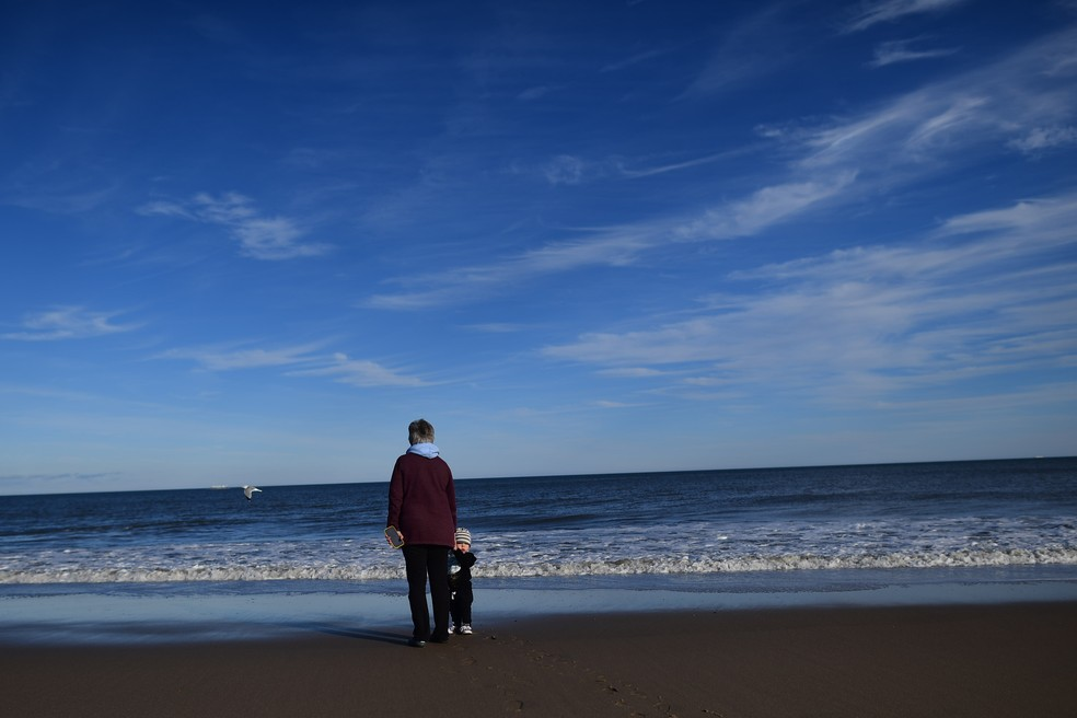 Mulher anda com neto na praia em Delaware, nos Estados Unidos, no dia 2 de janeiro. — Foto: Mark Makela/AFP